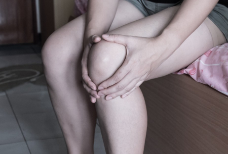 Woman holding her knee, appearing to be in pain