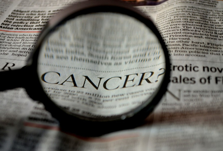 "The word ""Cancer"" is written in a newspaper and being magnified with a magnifying glass"